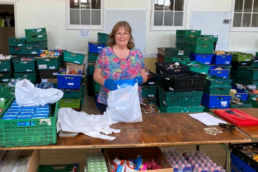 Jackie standing at a table packing food bags.