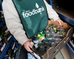 Foodbank volunteer with box of tins