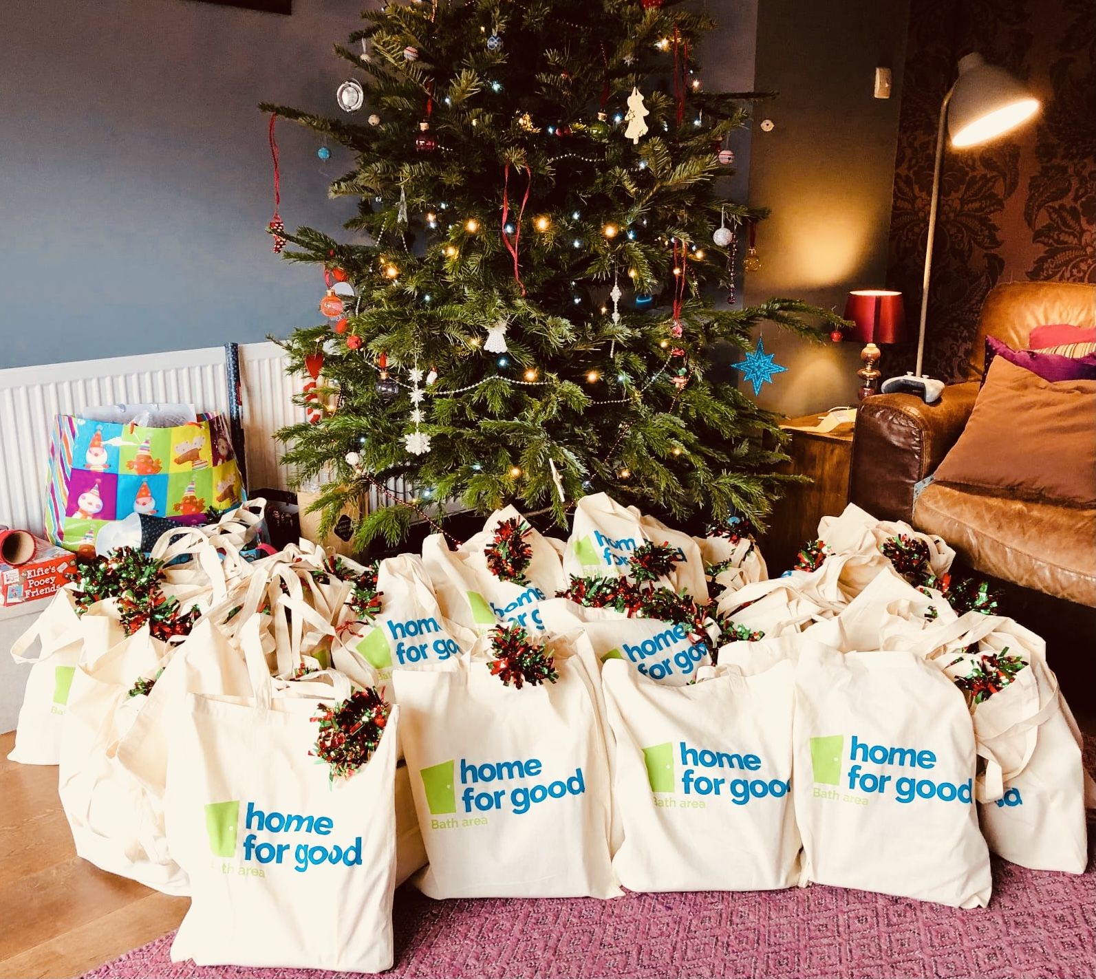 A decorated Christmas tree with filled goody bags around the base. The bags say Home for Good and have tinsel on the handles. These are thank you gifts for social workers.