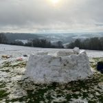 An igloo half built standing on a snow covered filed. Beautiful views across the Monkton Combe valley