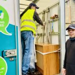 Two men, John and Ross, stand at the back of the Genesis Trust Furniture project van. One man, John, is inside tying down some furniture. The other man, Ross, stand outside the van and looks to the camera.