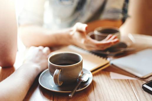 Talking at cafe table with coffee