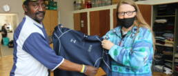 Anne, a volunteer at Genesis Trust, helps a client with clothes.