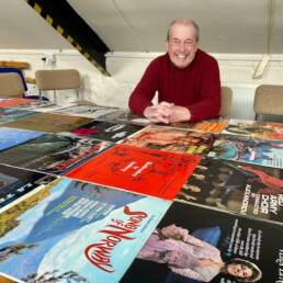 John Acton sitting in front of a number of music albums that he sold on eBay.